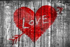Abstract heart pierced by an arrow with word LOVE on grunge wooden wall. Drawing of abstract heart pierced by an arrow with word LOVE on grunge wooden wall Stock Photo