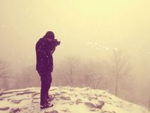 Abstract. Hiker in warm jacket enjoy view over snowy clouds. Winter mountain peak Stock Image