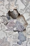 Abstract hole in cement on a stone wall. Abstract fragmentary hole in cement plaster on a stone wall Stock Images