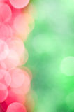 Abstract holiday background. Pink sparkles on blurred green background Stock Image
