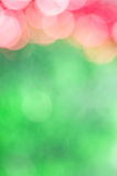 Abstract holiday background. Pink sparkles on blurred green background Royalty Free Stock Images