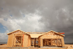 Abstract Home Construction Site and Ominous Clouds. Abstract of New Home Construction Site Framing and Dramatic Clouds Overhead stock photos