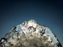 Abstract ice crystal formation against sun light and dark blue sky background with copy space. Abstract ice formation against sun light and dark blue sky royalty free stock image