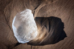 Abstract ice fragment on a sunny beach. An rounded piece of ice casting a fanciful shadow on the sand Stock Photography