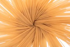 Abstract image from above of an Organic uncooked Brown Rice Spaghetti pasta arranged in a ceramic tall jar. Gluten-free and sodium-free alternative to stock photo