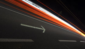 Abstract image, arrow and car lights trails. At night Royalty Free Stock Photos