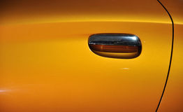 Abstract image from car door. Abstract image from a door and doorknob of a car, which shown as beautiful golden color, surface texture and the shape of doorknob Stock Photo