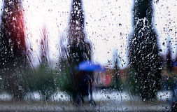 Abstract image of falling rain drops through the window with city background Stock Photos