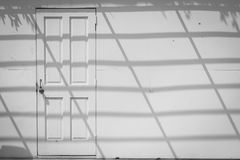 Abstract image of front view white wooden door on old white concrete wall with shadow shading on wall. Stock Image