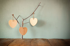 Abstract image of hanging wooden hearts over wooden background Royalty Free Stock Photography