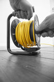 Abstract image of a man winding an extension cable Stock Image