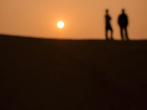Abstract image of 2 men at the desert in sunset time Royalty Free Stock Photos