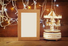 Abstract image of old vintage white carousel horses with garland gold lights and blank frame on wooden table. retro filtered image Stock Images
