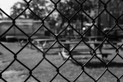 Back on the chain gang. Abstract image of an outdoor food court through a chain-link fence Royalty Free Stock Photography