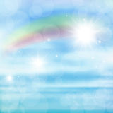 Abstract image of a rainbow on blue sky with sun glare. Royalty Free Stock Images