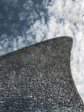 Abstract image of a sculpture against the textured sky. Fin or wave like sculpture against textures Stock Photos
