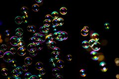 Soap bubbles from the bubble blower in dark or black background. Abstract image of soap bubbles from the bubble blower in dark or black background stock photos