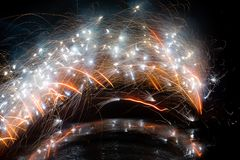 Abstract image of sparks from a fireworks fountain in an arc across the image with a slight reflection below royalty free stock photo
