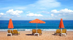 Abstract image with sun loungers and orange umbrellas from the sun on the beach on the seafront with waves relaxation, harmony,. Holidays - concept stock image