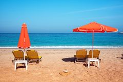 Abstract image with sun loungers and orange umbrellas from the sun on the beach on the seafront with waves relaxation, harmony,. Holidays - concept stock images