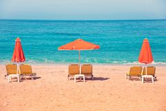 Abstract image with sun loungers and orange umbrellas from the s. Un on the beach on the seafront with waves relaxation, harmony, holidays - concept royalty free stock photography