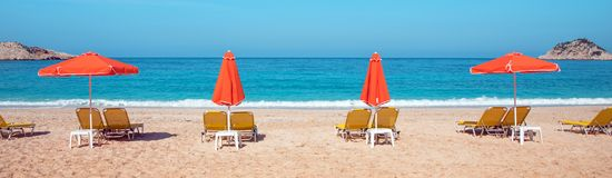 Abstract image with sun loungers and orange umbrellas from the s. Un on the beach on the seafront with waves relaxation, harmony, holidays - concept stock photography
