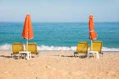 Abstract image with sun loungers and orange umbrellas from the s. Un on the beach on the seafront with waves relaxation, harmony, holidays - concept stock image