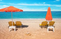 Abstract image with sun loungers and orange umbrellas from the s. Un on the beach on the seafront with waves relaxation, harmony, holidays - concept stock photo