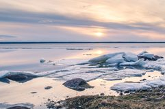 The abstract image of the sunset at the lake with the melting ice in early spring. Golden hour colours, grass and stones.  stock photography