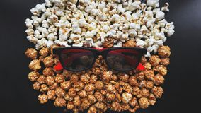 Abstract image of viewer, 3D glasses and popcorn on black background stock photography