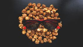 Abstract image of viewer, 3D glasses and popcorn on black background stock image