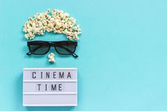 Abstract image of viewer, 3D glasses, popcorn and light box text Cinema time on blue paper background. Concept cinema movie and. Entertainment Flat lay Top view stock photo