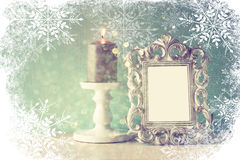 Abstract image of vintage antique classical frame and burning candle on wooden table with snowflakes overlay Royalty Free Stock Photography