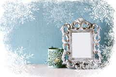 Abstract image of vintage antique classical frame and old lantern on wooden table with snowflakes overlay Royalty Free Stock Photography