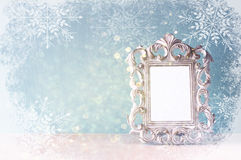 Abstract image of vintage antique classical frame on wooden table with snowflakes overlay Stock Photo