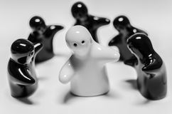 Abstract image of white ceramic doll standing among black cerami Stock Photography