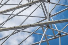 Abstract image of white steel struts and supports in front of a white-blue sky. Abstract royalty free stock photos