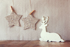 Abstract image of white wooden reindeer and glitter stars hanging on rope over glitter silver background Stock Photo