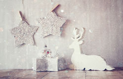 Abstract image of white wooden reindeer and glitter stars hanging on rope over glitter silver background. retro filtered Royalty Free Stock Photo