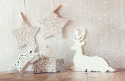 Abstract image of white wooden reindeer and glitter stars hanging on rope over glitter silver background. retro filtered Royalty Free Stock Photos