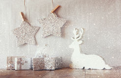 Abstract image of white wooden reindeer and glitter stars hanging on rope over glitter silver background. retro filtered Royalty Free Stock Images