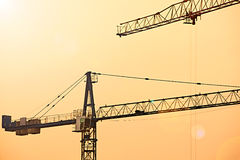 Abstract Industrial background with construction cranes silhouettes over amazing sunset sky Royalty Free Stock Photography