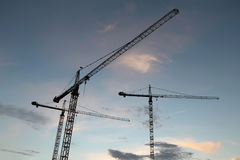 Abstract Industrial background with construction cranes silhouettes over sunset sky Stock Images