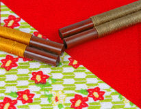 Abstract Japanese still life. Two pairs of chopsticks on a specific piece of red Japanese fabric Stock Image