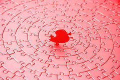 Abstract of a jigsaw in red and pink with the last piece upstanding Royalty Free Stock Photo