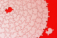 Abstract of a jigsaw in red and pink with one missing piece laying aside. Shallow DOF, focus is on the hole - adobe RGB Stock Photo