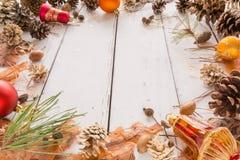 Abstract Kerstmiskader met kegels, pijnboomschors, eikels, en speelgoed Witte Houten Achtergrond Stock Afbeelding