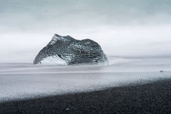 An abstract large piece of glacier ice sits on a black sand beach in Iceland Royalty Free Stock Images