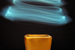 Abstract light. Light trails over golden pot Royalty Free Stock Image