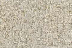 Abstract light beige grainy background with the texture of coarse grained new decorative plaster. Construction and repair. Abstract light beige grainy stock image